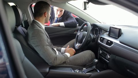 Young man sitting in car. Auto business, car sale, technology and people concept - happy male with car dealer in auto show or salon. Young man with a salesman in a motor show.