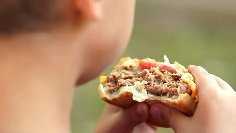 Close up of huge hamburger in hands of child