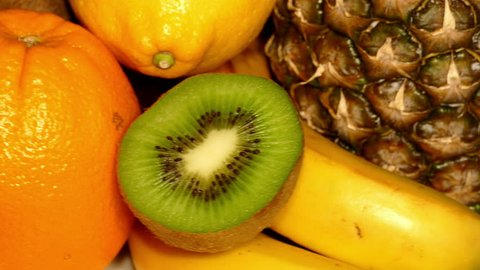 Ripe tropical fruit (healthy food)  – pineapple, kiwi, orange, coconuts, lemon, bananas rotating, front shot, extreme close up, loop (ultra hd 3840x2160)
