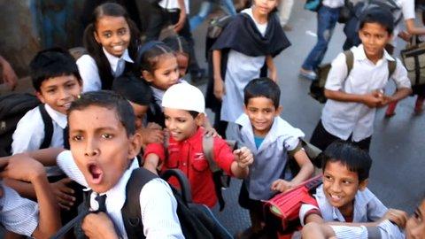 MUMBAI, INDIA - 14 JANUARY 2015: Group of school children running around and smiling at street.