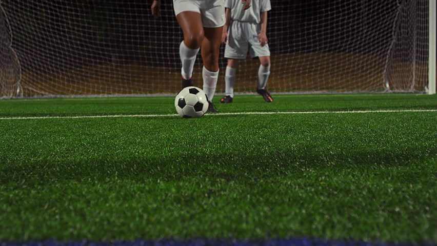 A female soccer player dribbles down the field during a game at night #11951420
