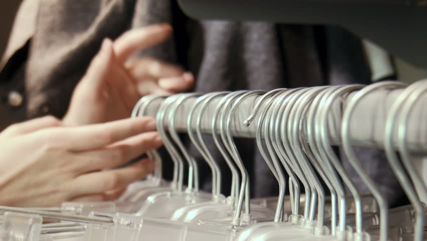 Female looking for a suitable skirt and blouse in shop on hangers. Clothes shop close view of hangers with clothes | Shutterstock HD Video #11961500