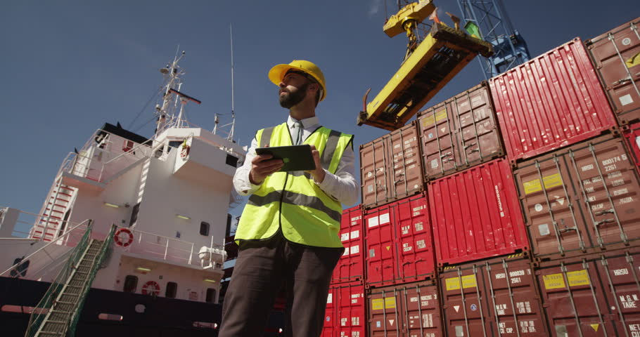 A young manager doing inspection rounds through an industrial harbor working on a digital tablet. Shot on RED Epic. | Shutterstock HD Video #11962457