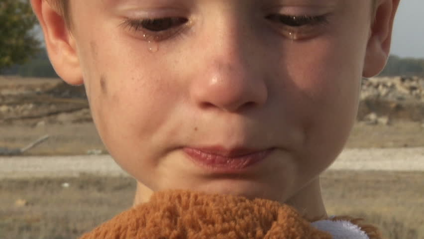 dirty little orphan boy close-up crying and petting a stuffed toy on the background of the ruins of the destroyed  houses
