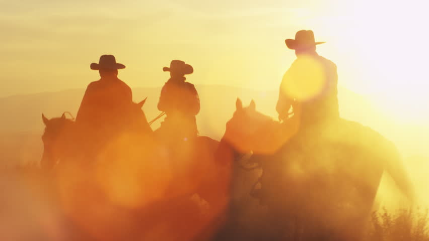 Cowboys galloping into dusk. Lens flare is visible. | Shutterstock HD Video #11965031