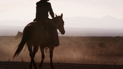 Nevada Desert - May 2013: Silhouette shot of a cowboy walking his horse with dust blowing by. Second cowboy enters