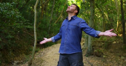 Super slow motion of young man breathe and enjoy a green forest with the raised arms in 4k (close up)