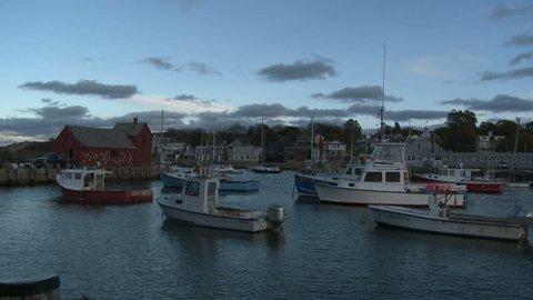 Boston, Massachusetts - September, 2012: Panning shot at sundown of Rockport Harbor from Motif Number 1, a famous red fishing shack on Bradley Wharf.