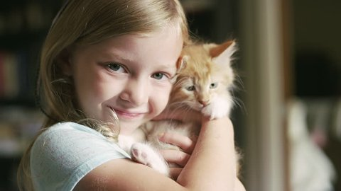 A little girl holding a kitten and smiling