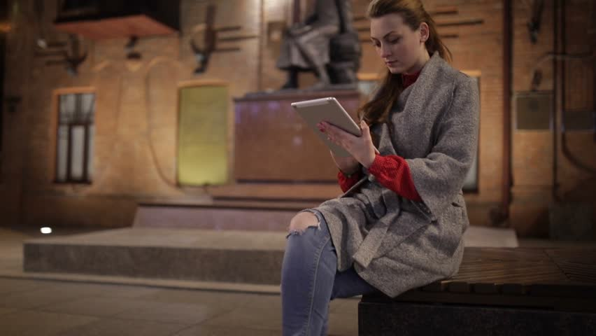 Beautiful woman in a coat with a clipboard on a bench in the evening. | Shutterstock HD Video #12009410