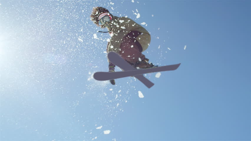 SLOW MOTION CLOSEUP: Freestyle skier jumping big kicker and flying over the sun in snowy mountains | Shutterstock Video #12010307