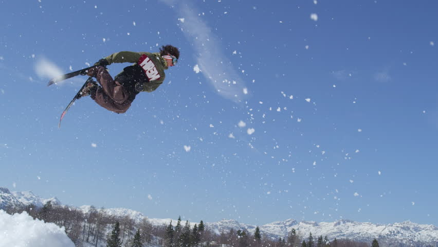 SLOW MOTION CLOSE UP: Freestyle skier jumping and spinning in beautiful snowy mountains #12010310