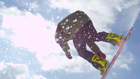 SLOW MOTION CLOSE UP: Extreme snowboarder jumping big air kicker in sunny winter in mountain snow park