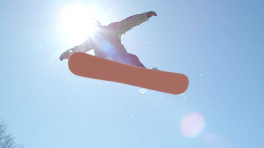 SLOW MOTION CLOSE UP: Snowboarder jumping over the sun in snowpark on a beautiful sunny day in snowy ski resort