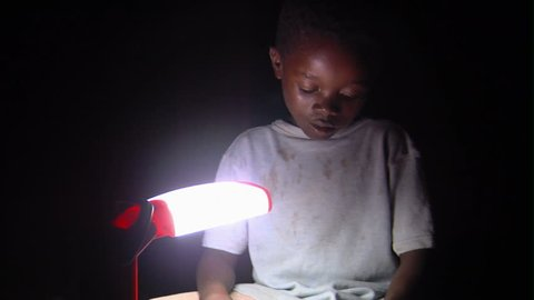 Kenya, Africa - April, 2013: Medium shot of child reading by lamp