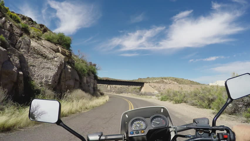 Point of view vehicle driving shot overlooking handlebars of a motorcycle. Motorcycle crosses under a train bridge on a canyon road in 4K format. | Shutterstock HD Video #12079211