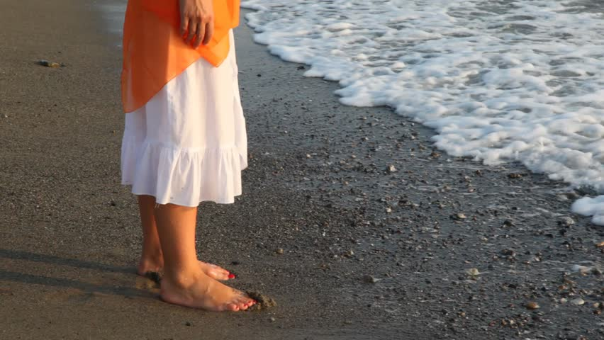 woman in white douses barefoot feet in waves of sea surf