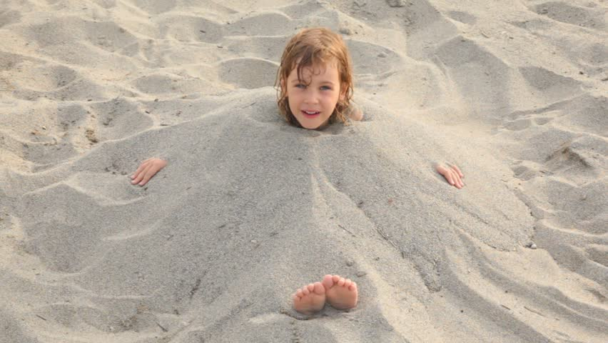 girl on coast buried by her brother who adds sand on beach with prominent feet hands and head