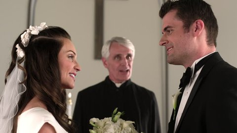 Dolly shot moving around a bride and groom at the front of a chapel. They kiss and smile. Rack focus to the preacher.