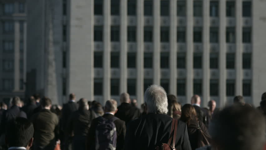 Slow motion of a large crowd of anonymous people in front of grey building in 4K. Large crowd of commuters and pedestrians walk across London Bridge to the City of London. Framed for graphics.