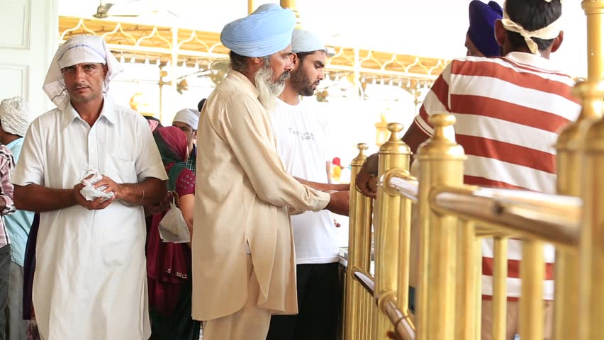 AMRITSAR, INDIA - SEPTEMBER 27, 2014: Unidentified Sikhs and indian people visiting the Golden Temple in Amritsar, Punjab, India. Sikh pilgrims travel from all over India to pray at this holy site. | Shutterstock HD Video #12098450