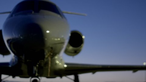 Man walking past parked private jet (Cessna Citation)