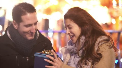 Young man surprise his girlfriend with a Christmas gift outdoors at Christmas fair. Shot on RED Epic.