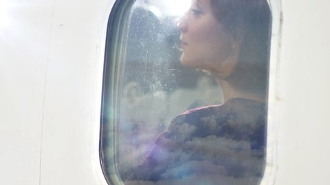 Young women looks through an airplane window and smiles during flight. Shot on RED Cinema Camera in 4K (UHD).