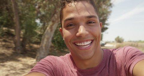 Cute Hispanic man spinning selfie outside