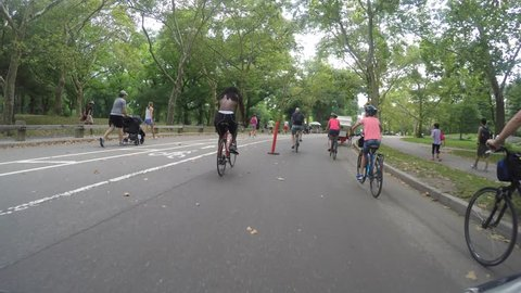 NEW YORK CITY, CENTRAL PARK, JULY 2015 - 4K DX POV GoPro Biking Driving Plate #2 - POV shot of bike cruising past people exercising and other bicycles towards the exit to upper east side