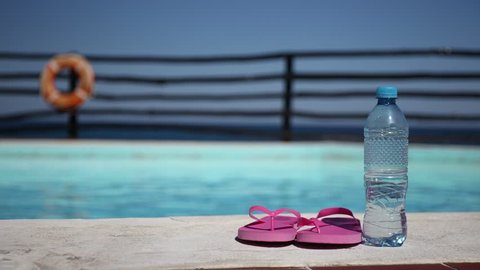 Plastic bottle with pure water and slippers near swimming pool at poolside