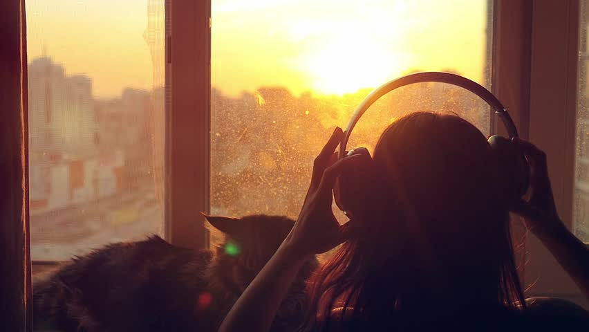 Young woman wears headphones looking on the window and relaxing with her lovely Maine Coon cat at window with blurred city background at sunset in slowmotion. 1920x1080