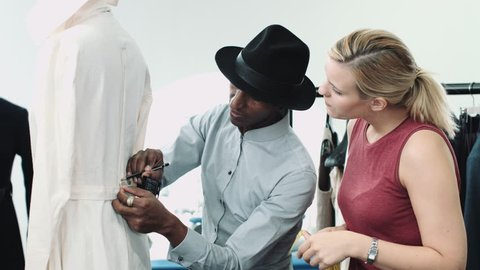 Fashion designer at work in studio training apprentice