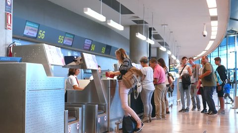 VALENCIA, SPAIN - OCTOBER 11, 2015: Airline passengers checking in at an airline counter in the Valencia Airport. About 4.98 million passengers passed through the Valencia Airport in 2014.