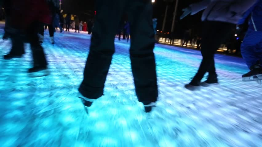 Legs on skates slide by surface of icerink illuminated from inside.