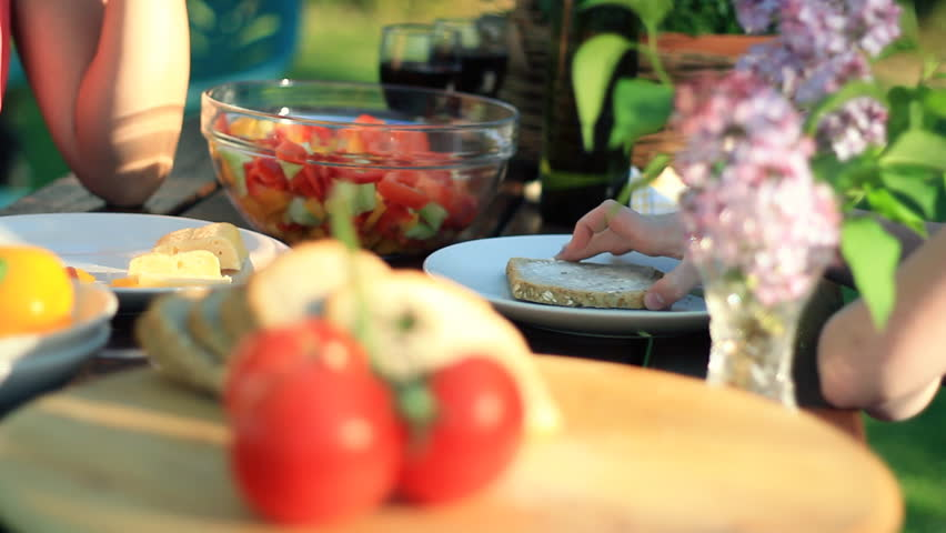 Family hands eating food from the table in the garden, dolly shot