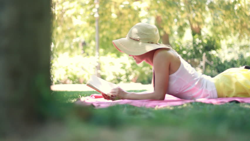 Young woman reading book in park, dolly shot