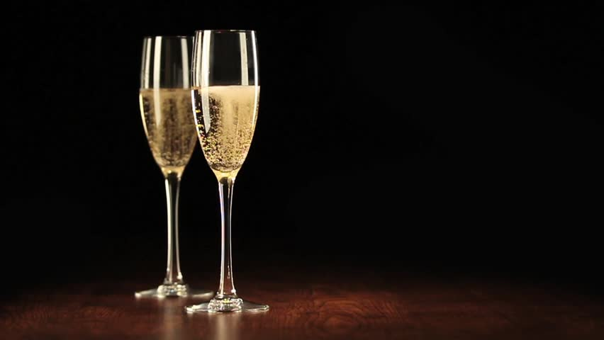 two glasses with champagne on a wooden table