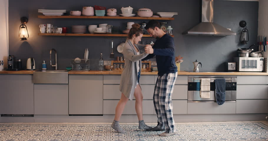 Happy young couple newly wed dancing listening to music in kitchen wearing pajamas coffee morning at home having fun