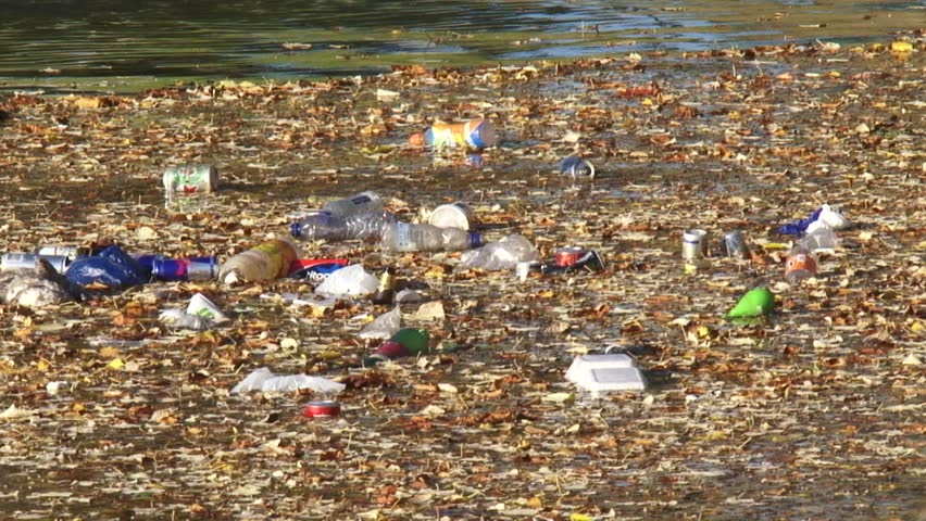 Litter, pet bottles and beverage cans, floats on water surface in city canal - full screen #12283940