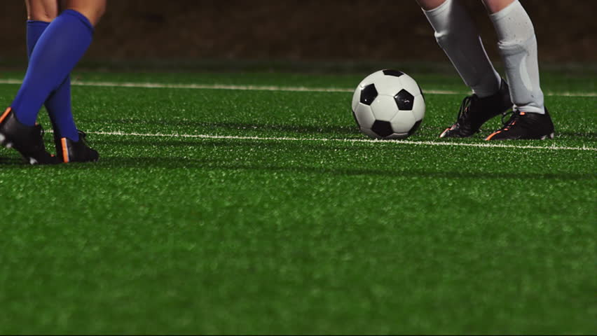 Close up of female soccer players dribbling down the field at night #12305120
