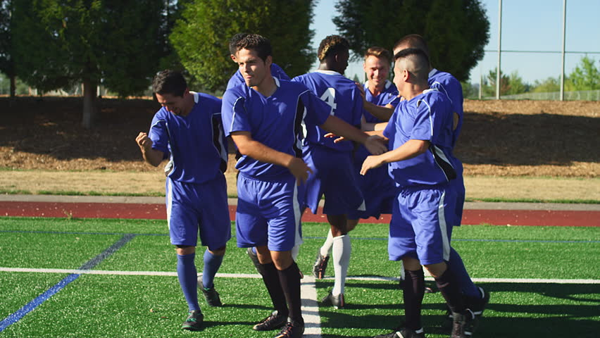 A soccer player makes a goal and the team hugs and celebrates