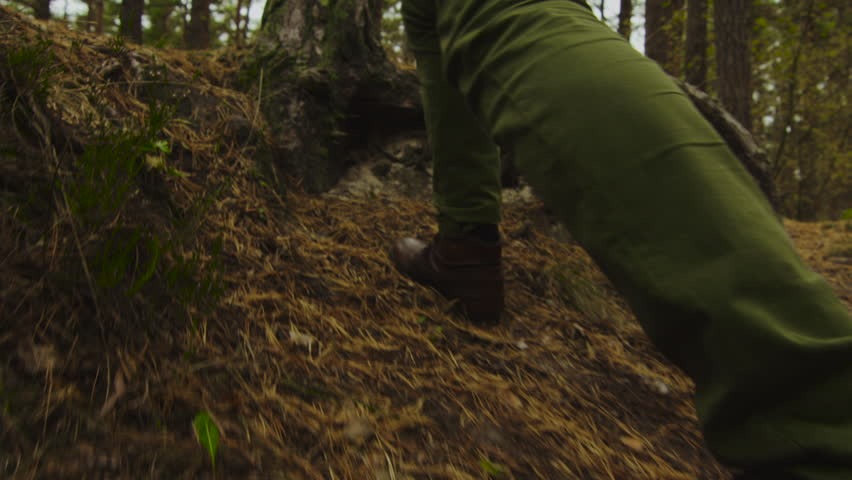 Hiker in close-up slow motion leg shot walks uphill in the forest in autumn. Shot on RED Cinema Camera in 4K (UHD).