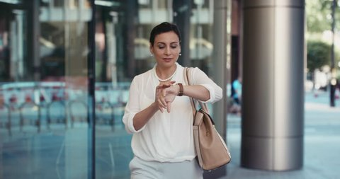 Smart Middle Eastern businesswoman using smartwatch commuting to work entering glass corporate building smiling