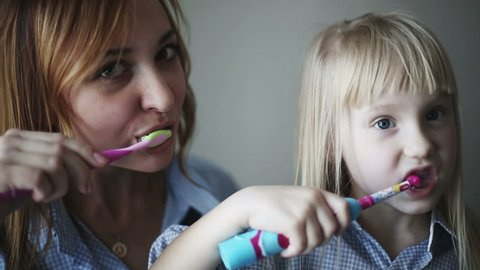 Happy family and health: Mother And Daughter Brushing Teeth Together