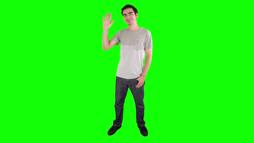 Young adult saying hello with his hand on a green screen chroma key background easy to replace with your content. Shot in 4K UHD resolution.