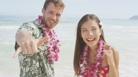 Happy couple of tourists standing on Hawaiian beach at their Hawaii vacation. Asian woman and Caucasian man wearing flower lei garland and Aloha clothing showing Shaka hand sign on travel. RED EPIC.