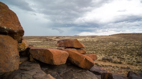 A linear timelapse of a rocky Karoo landscape with wide open vistas and stormy clouds gathering as a thunderstorm approaches while the camera moves in behind the rocks in the foreground. 4K