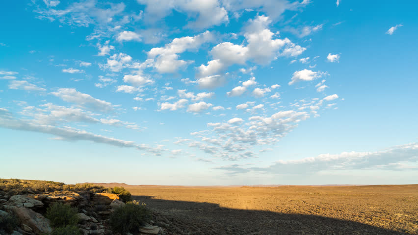TRIPOD SHADOW?? A static timelapse of a typical rocky Karoo landscape as the sun rises to light up the scenery with slow moving clouds moving in over a bright blue sky. 4K