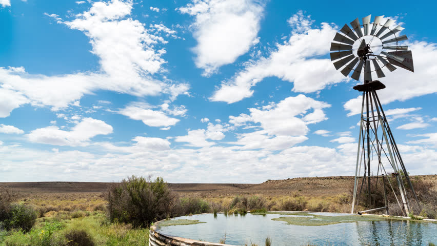 A linear midday timelapse of a windmill blowing in the wind next to and old zinc farm dam with scattered clouds against a bright blue sky in a typical Karoo landscape. 4K